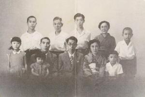 Front Row: Shoshichi (21) with Father Kyuzo (49) and Mother Yoshie (45), and Kazuo (7). Two girls on the left are cousins, Chieko and Kazumi Tanaka. Rear Row:   Hisashi (15), Uncle Eizo Tanaka, Toshinori (18), Aunt Tsune Yumoto, Cousin Minoru Tanaka